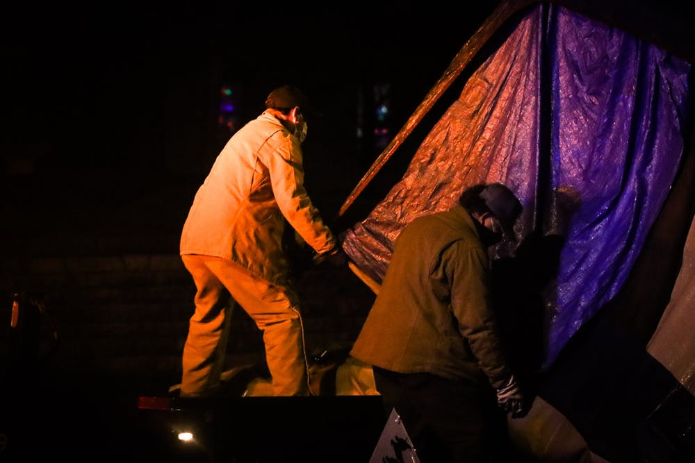 <p>City of Bloomington employees lift a tent on a truck at Seminary Park on Jan. 14. One person experiencing homelessness was permitted to stay in the park overnight, along with two volunteers who stayed for support.</p>