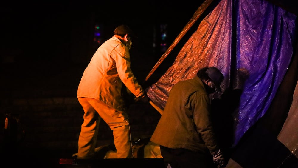 City of Bloomington employees lift a tent on a truck at Seminary Park on Jan. 14. One person experiencing homelessness was permitted to stay in the park overnight, along with two volunteers who stayed for support.