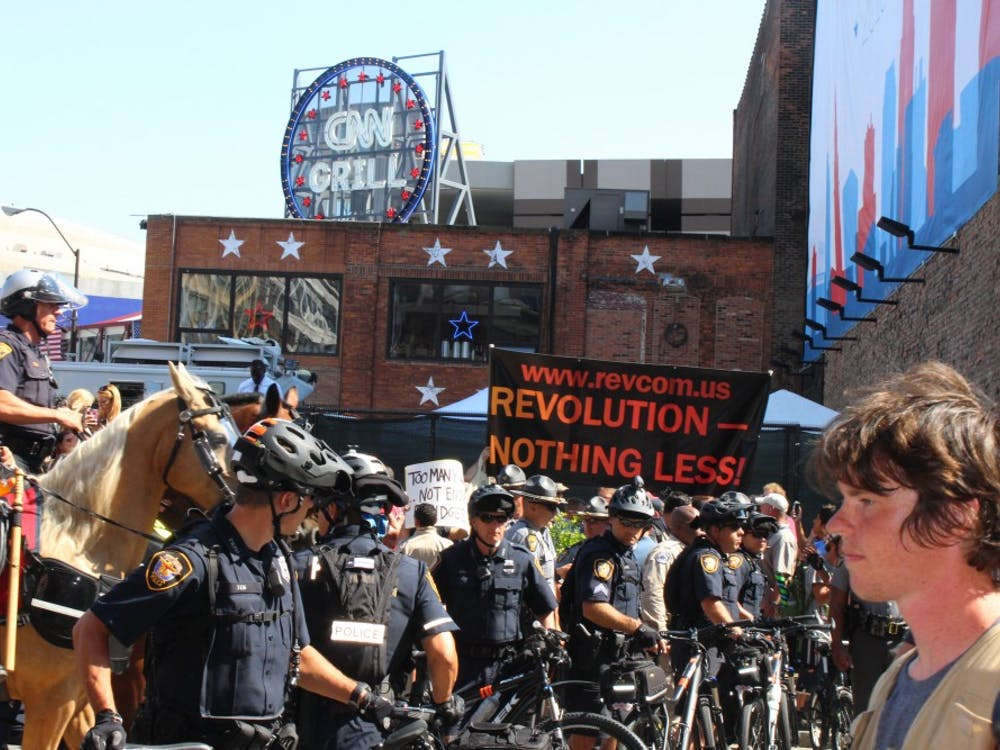 Police officers on horses order crowds to disperse after an American flag burning demonstration sparked controversy on Fourth and Prospect during the third day of the Republican National Convention.