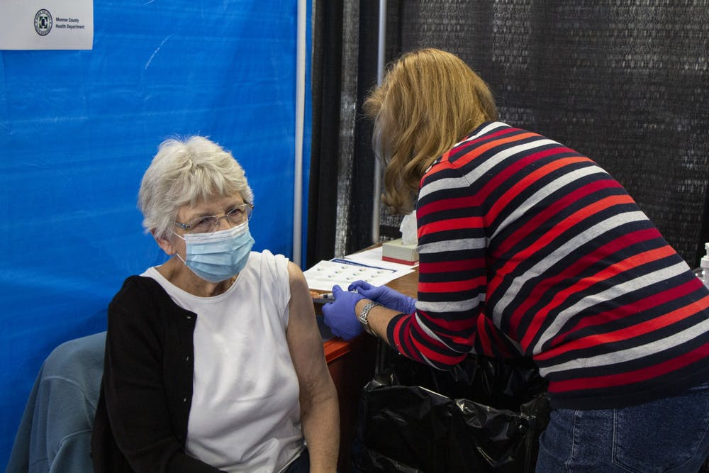 <p>IU Health nurse Anne Fuson gives a second dose of the Moderna COVID-19 vaccine to Iva Gloss on Feb. 24 at the Monroe Convention Center. During a meeting Friday, the City of Bloomington announced that out of state students eligible to receive the COVID-19 vaccine can do so in Indiana. </p>