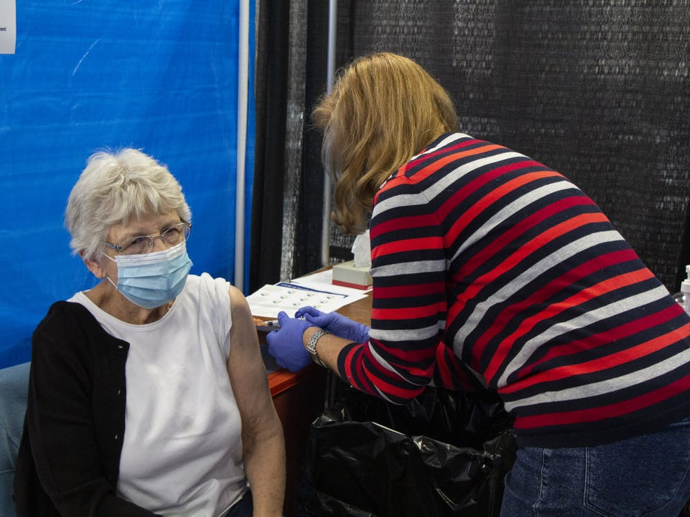 IU Health nurse Anne Fuson gives a second dose of the Moderna COVID-19 vaccine to Iva Gloss on Feb. 24 at the Monroe Convention Center. During a meeting Friday, the City of Bloomington announced that out of state students eligible to receive the COVID-19 vaccine can do so in Indiana.
