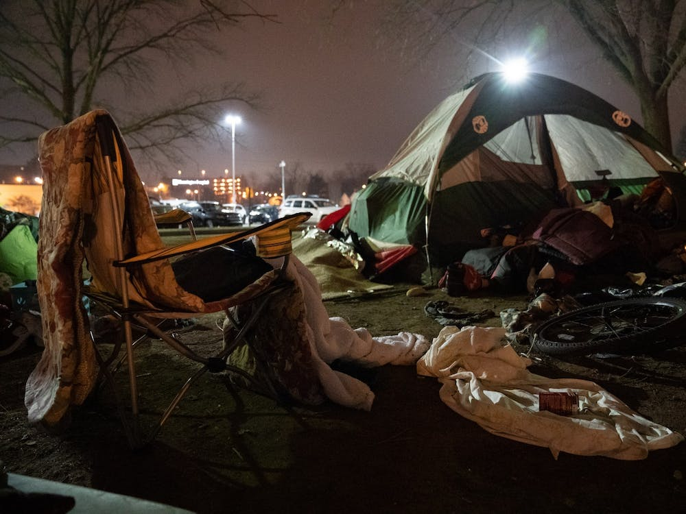 Belongings of people experiencing homelessness lie in the grass on Monday at Seminary Park. The Bloomington City Council approved a rezoning petition to allow Wheeler Mission to expand their offerings to people experiencing homelessness Wednesday.