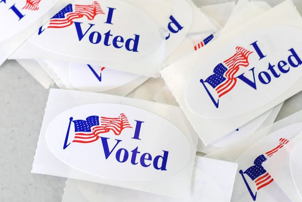 <p>A pile of stickers reading &quot;I Voted&quot; sits on a table. </p>