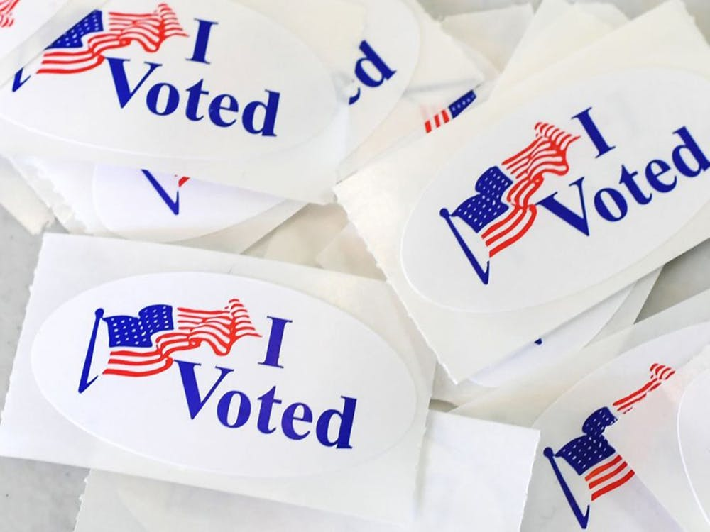 """A pile of stickers reading """"I Voted"""" sits on a table."""