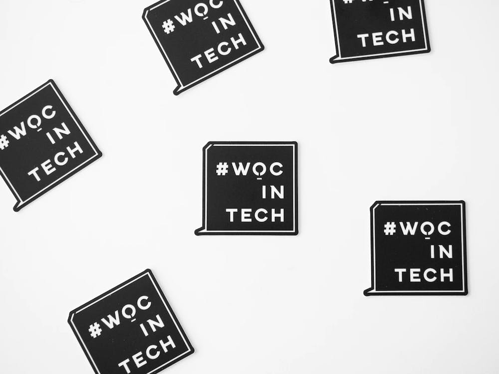 """A graphic displays the message """"#WOCinTech,"""" supportive of women of color in tech industries."""