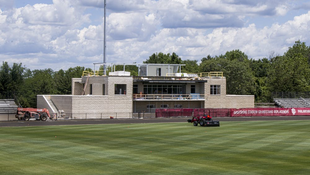 A groundskeeper mows the lawn June 25 as construction workers renovate Bill Armstrong Stadium. The stadium is home to the annual Little 500 race and IU's men's and women's soccer teams.