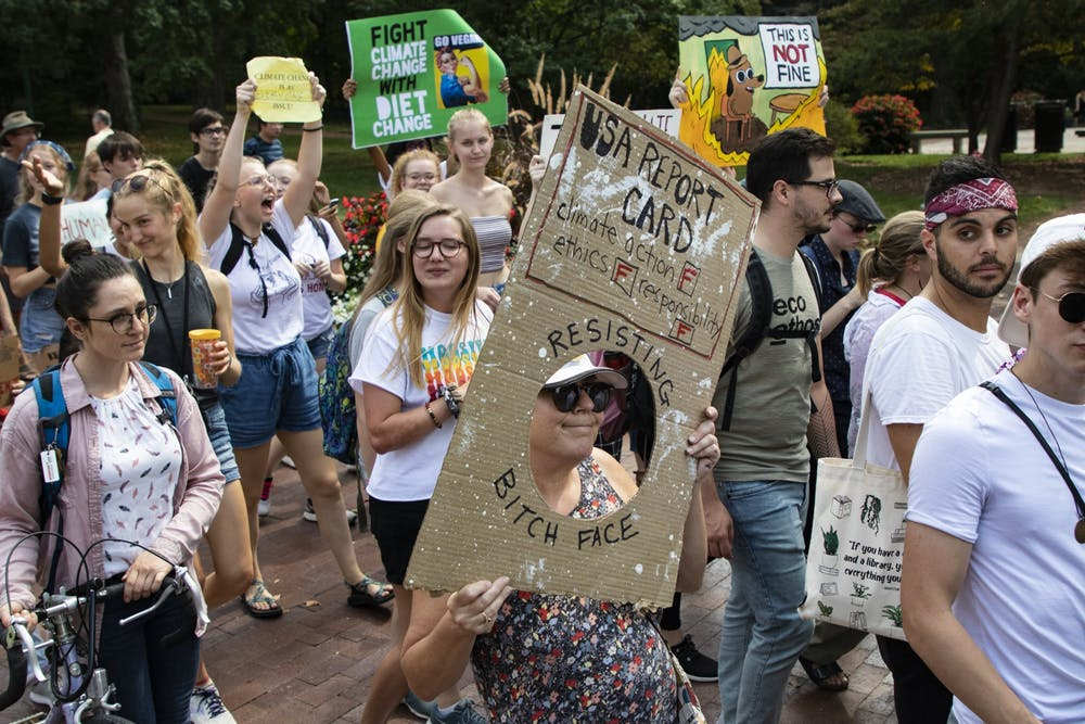 <p>Protestors walk with signs during the Bloomington Climate Strike rally Sept. 20, 2019, in front of Franklin Hall. President Joe Biden&#x27;s climate plan includes reaching net-zero emissions by 2050.</p>