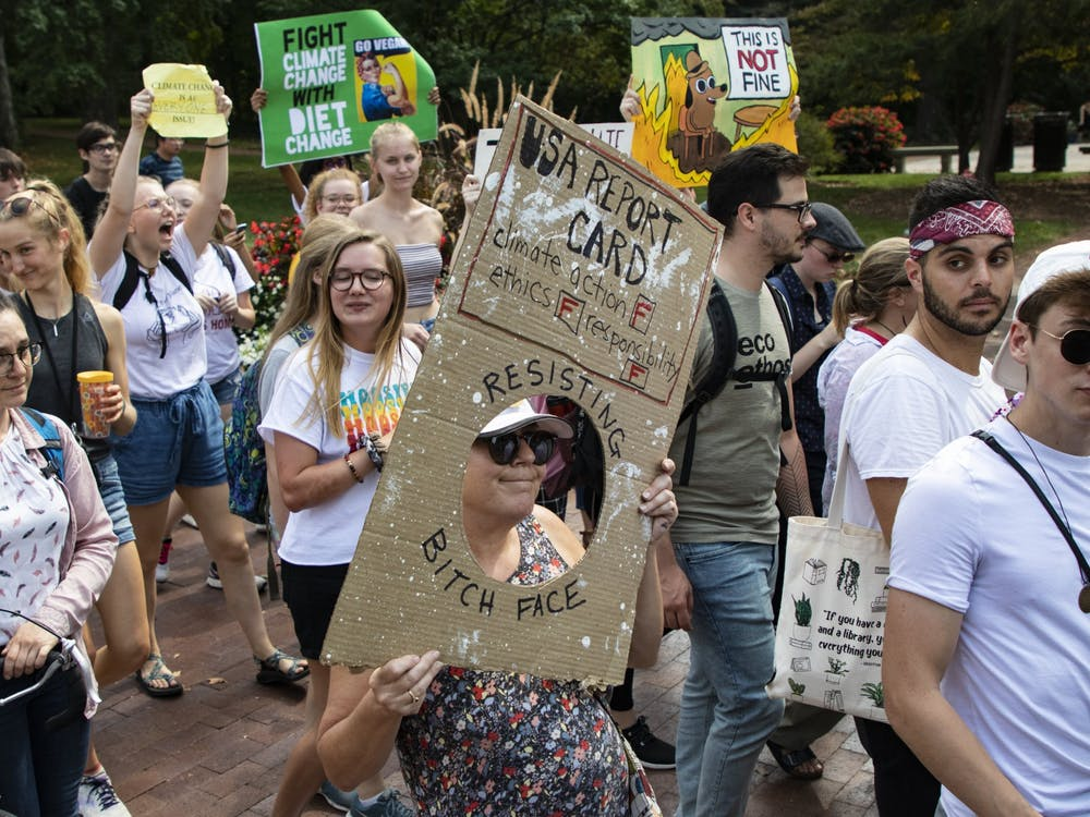 Protestors walk with signs during the Bloomington Climate Strike rally Sept. 20, 2019, in front of Franklin Hall. President Joe Biden's climate plan includes reaching net-zero emissions by 2050.