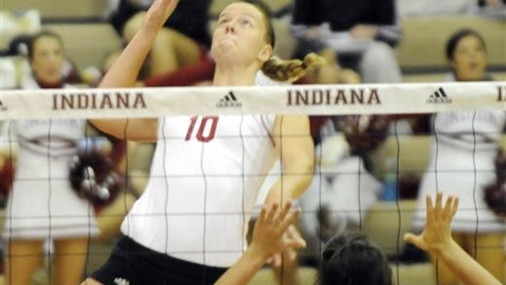IU sophomore Ashley Benson spikes on Ball State sophomore Hannah Sullivan during the TIS Bookstore Invitational on Aug. 19 at University Gym. IU swept Ball State 3-0.