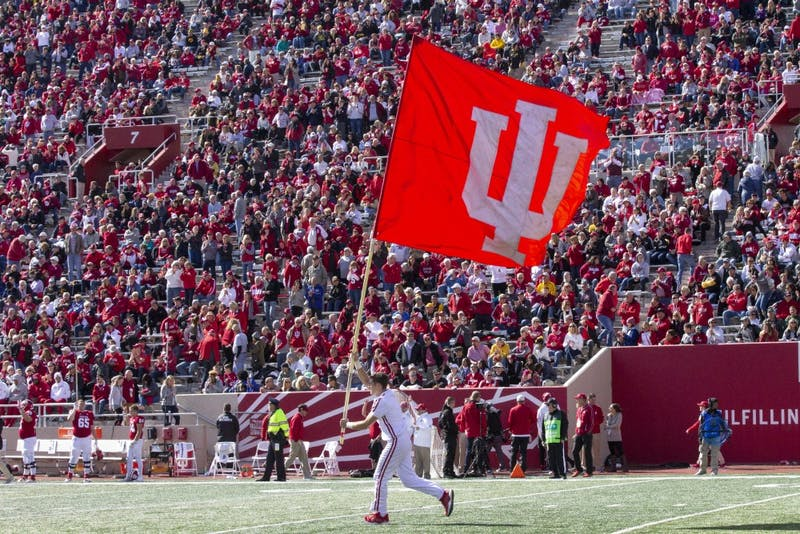 Gavin Schmuckler runs the IU flag across the field Oct. 13, 2018, at Memorial Stadium. IU swim and dive signee Emily Weiss became the 11th swimmer in Indiana history to ever win four state championships Feb. 9.