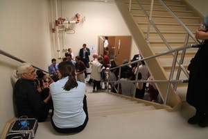 People attending the School of Public and Environmental Affairs networking event in Franklin Hall sit and stand in the stairwell due to a tornado warning. The event was taking place in Presidents Hall, which is lined with large windows.