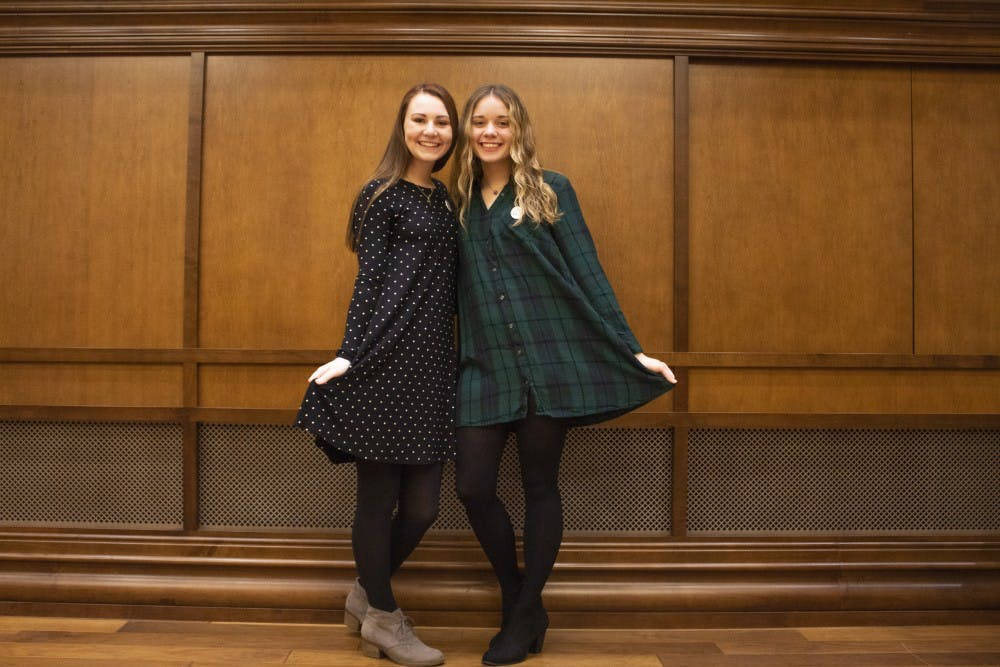 "<p>Olivia Oster, left, and Jenna Crawford, right, wear dresses with their ""Ask Me About My Dress"" buttons Nov. 28 in Presidents Hall. They are members of the Dressember Foundation. The foundation encourages every member to wear a dress or tie every day of December to raise awareness for trafficking victims around the world.</p>"