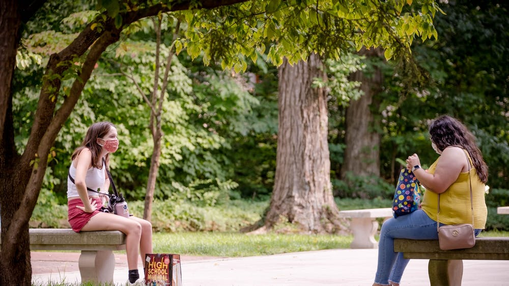 Sophomores Yatziri Moreno, left, Meg Heinisch, right, meet Aug. 24 behind Bryan Hall. They sat at a safe distance and wore a mask due to the coronavirus pandemic.