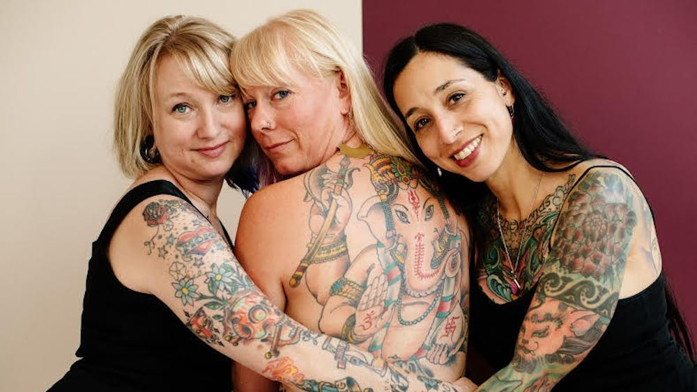 Alicia Suarez, director of Women's, Gender and Sexuality Studies at Depauw University, stands on the right while posing for a photo taken by Natasha Komoda, the founder of Femography. Suarez said she has faced discrimination because of her tattoos.