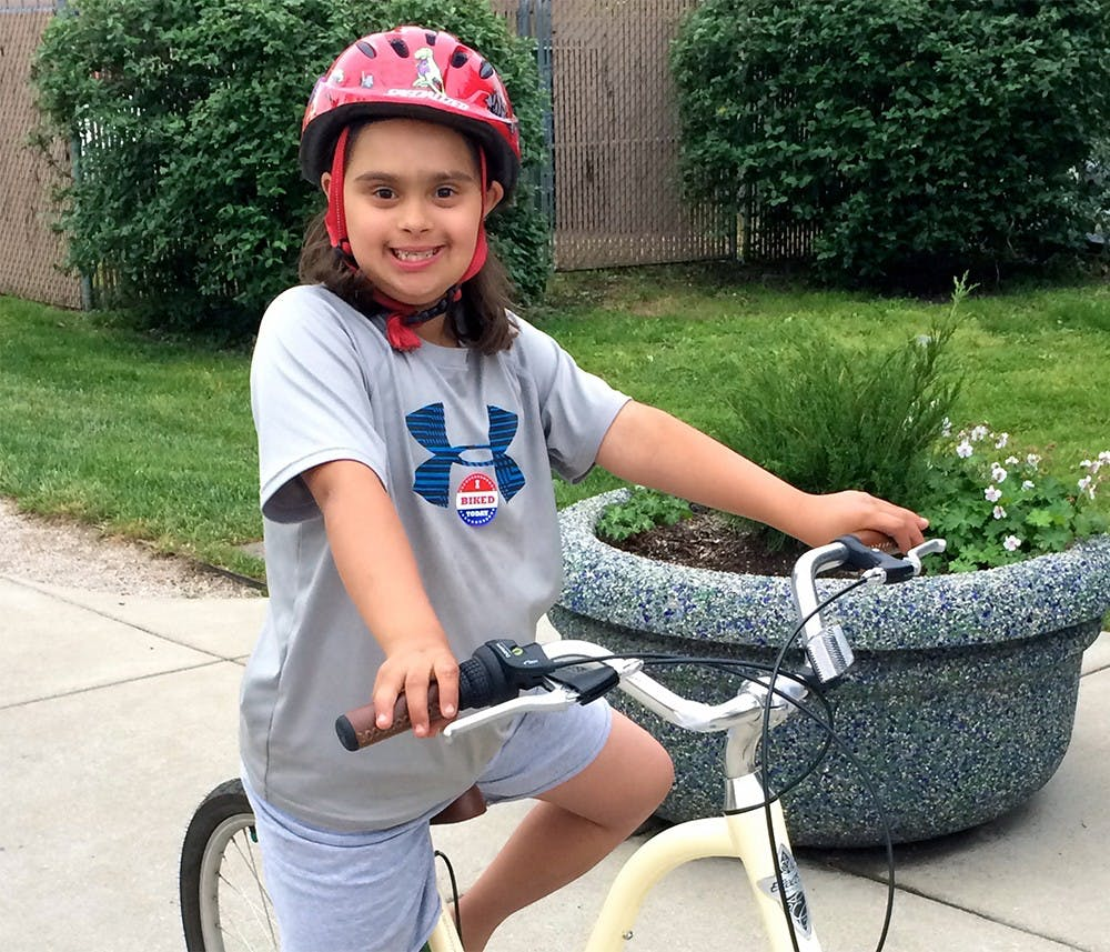 """Ava Butske sits on her bike at Bloomingfood's annual """"Bike to Work Day Block Party"""" Saturday at the Near West Side Bloomingfoods location. Ava learned how to ride at an iCan Bike camp in Greenwood, Ind."""