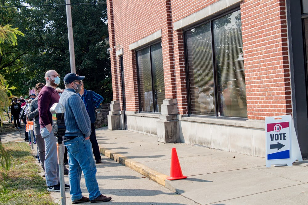 <p>Voters wait in line to vote Tuesday at a polling location at 401 W. 7th St. Tuesday was the first day of early voting in Indiana.</p>