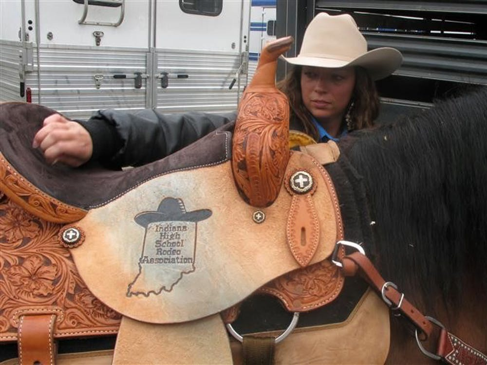 Morgan McKinney, 18, cleans her saddle as she prepares Brady, her 19-year old horse, to compete in the pole bending event at the Illinois Tri-State Rodeo. Morgan finished the season first place in pole bending for the state of Indiana last year.