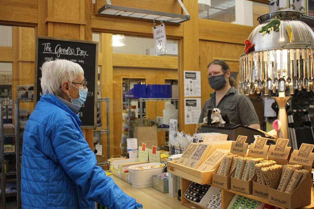 <p>Bloomington resident Pam Gilliatt, 77, wears a mask while browsing in Goods for Cooks and talking to assistant manager Jacob Leaf. The Monroe County Health Department extended its mask mandate until May 28.</p>