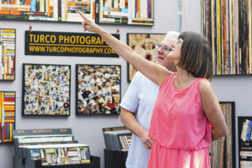 <p>Visitors to Fouth Street Festival of the Arts and Crafts stop at Greg Turco's booth Sunday morning. Artists fill Fourth and Grant streets with types of art ranging from photography to ceramics.&nbsp;</p>