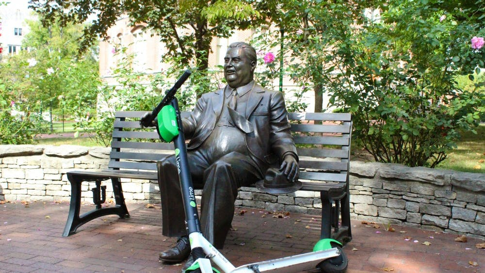 A Lime scooter rests in the hands of a statue of Herman B Wells on Sept. 22 near Wylie Hall. Students frequently use scooters as transportation on campus.