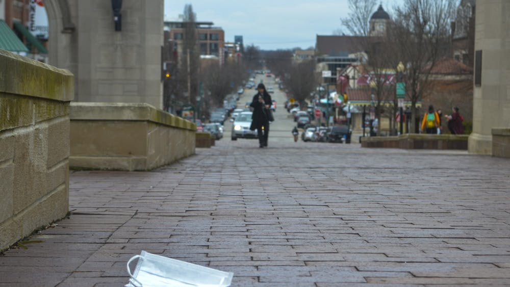 A surgical mask rests on the ground March 12 in front of Sample Gates. IU is asking that as few students be on campus as possible during the upcoming winter intersession due to the coronavirus.