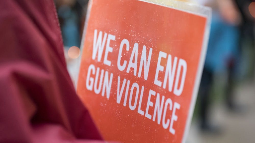 Ann Edmonds holds a sign at the Sunday vigil honoring victims of the Las Vegas shooting. The signs were distributed by Moms Demand Action, a group advocating stricter gun laws.