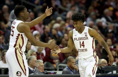 Florida State University teammates Terance Mann and Mfiondu Kabengele celebrate March 14 during a 65-63 overtime win against Virginia Polytechnic Institute and State University during quarterfinals of the ACC Tournament at Spectrum Center in Charlotte, North Carolina.