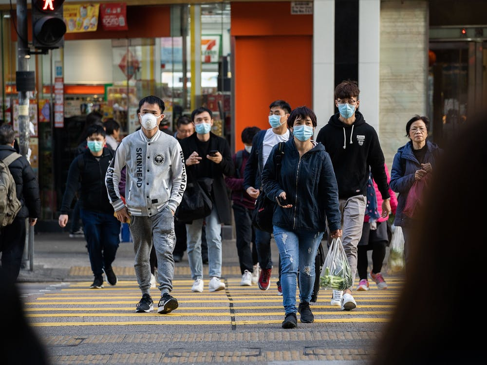 Chinese residents wear surgical masks Jan. 30 while crossing the road in order to prevent the spread of the Wuhan corona virus in Hong Kong. IU suspended travel to China in response to the World Health Organization declaring coronavirus to be a Public Health Emergency of International Concern.