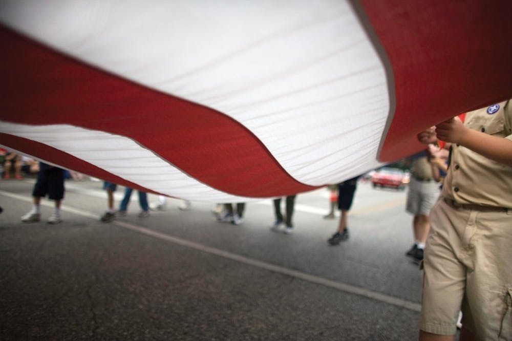 <p>Participants in the Independence Day parade carry the American flag July 4, 2007. During the Independence Day Reverse Parade the entries will remain stationary while the spectators drive or bicycle past them.</p>