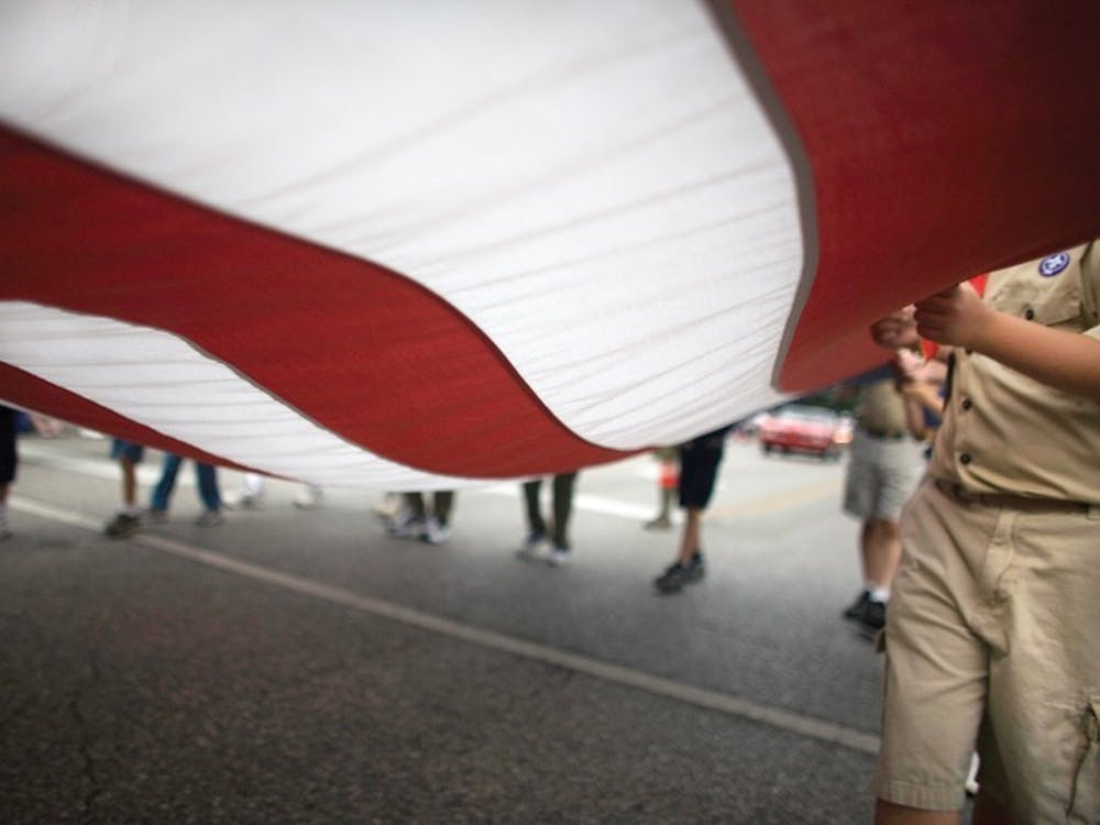 Participants in the Independence Day parade carry the American flag July 4, 2007. During the Independence Day Reverse Parade the entries will remain stationary while the spectators drive or bicycle past them.