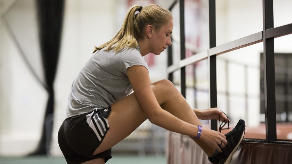 Junior Lexa Barrott laces up her sneakers before the start of track and field practice Friday afternoon in Gladstein Fieldhouse. Barrott, a distance runner, ran as an alternate in the Big Ten Championships during the 2016-17 season.