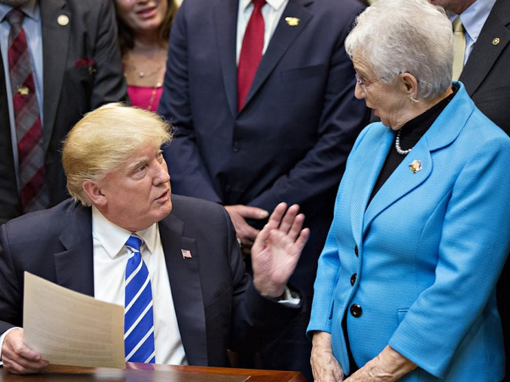U.S. President Donald Trump speaks next to Representative Virginia Foxx, a Republican from North Carolina, right, during a bill signing ceremony in the Roosevelt Room of the White House on March 27 in Washington, D.C.