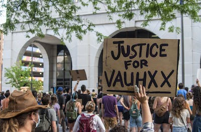 A protester holds up a sign July 6 in front of the Charlotte Zietlow Justice Center. Vauhxx Booker was the victim of a racist attack July 4 near Monroe Lake.