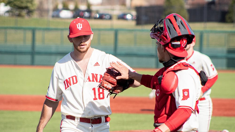 Redshirt senior catcher Collin Hopkins high fives senior pitcher Braden Scott during a game against Purdue on Saturday at Bart Kaufman Field. The Hoosiers won two of three games against the Purdue Boilermakers this weekend.