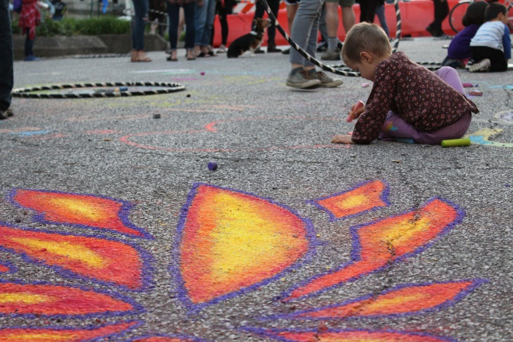 <p>Children play with chalk during the 2018 Lotus World Music &amp; Arts Festival on Sept. 28.</p>