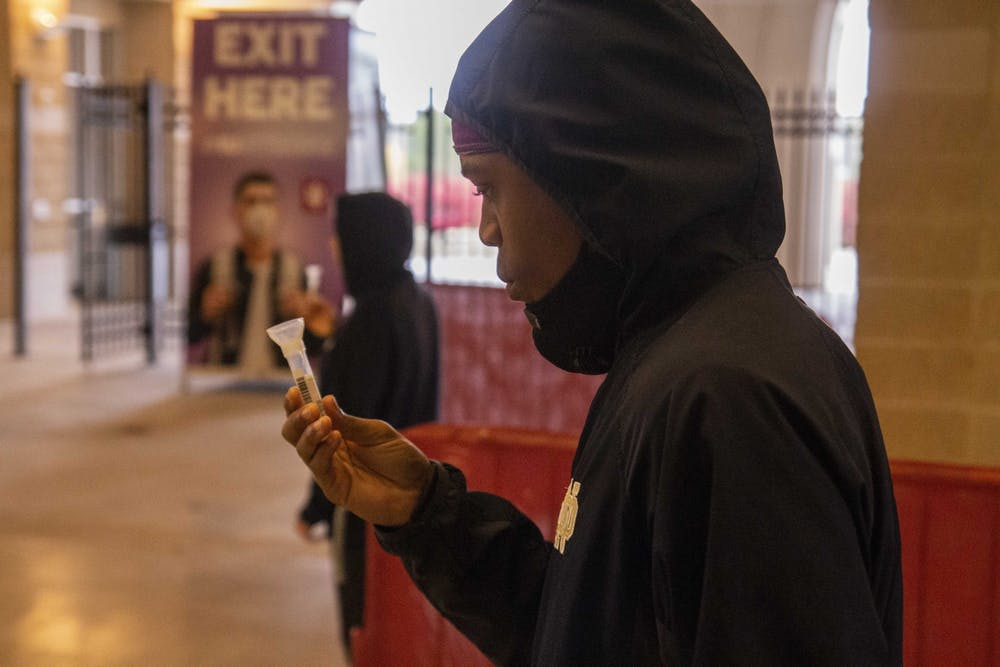 <p>Sophomore K.J. Helloms checks the levels of a saliva sample for COVID-19 mitigation testing Oct. 15, 2020, at Memorial Stadium. IU&#x27;s two indoor locations for mitigation testing are the IU Auditorium and Ray E. Cramer Marching Hundred Hall.</p>