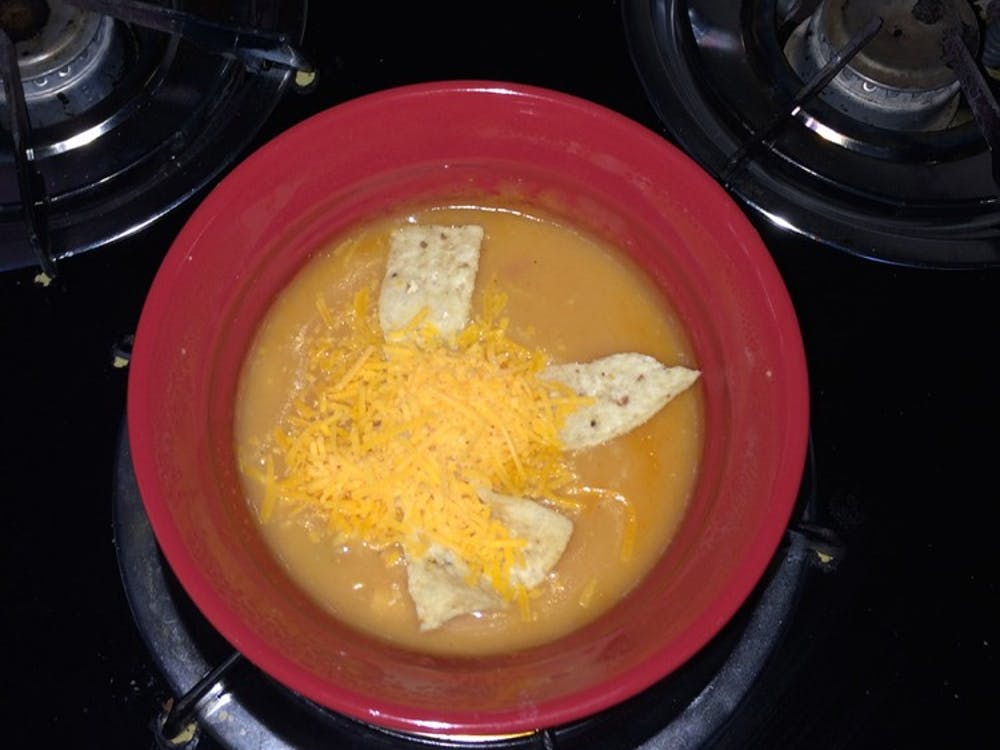 A bowl of chicken tortilla soup sits on a burner after being prepared.
