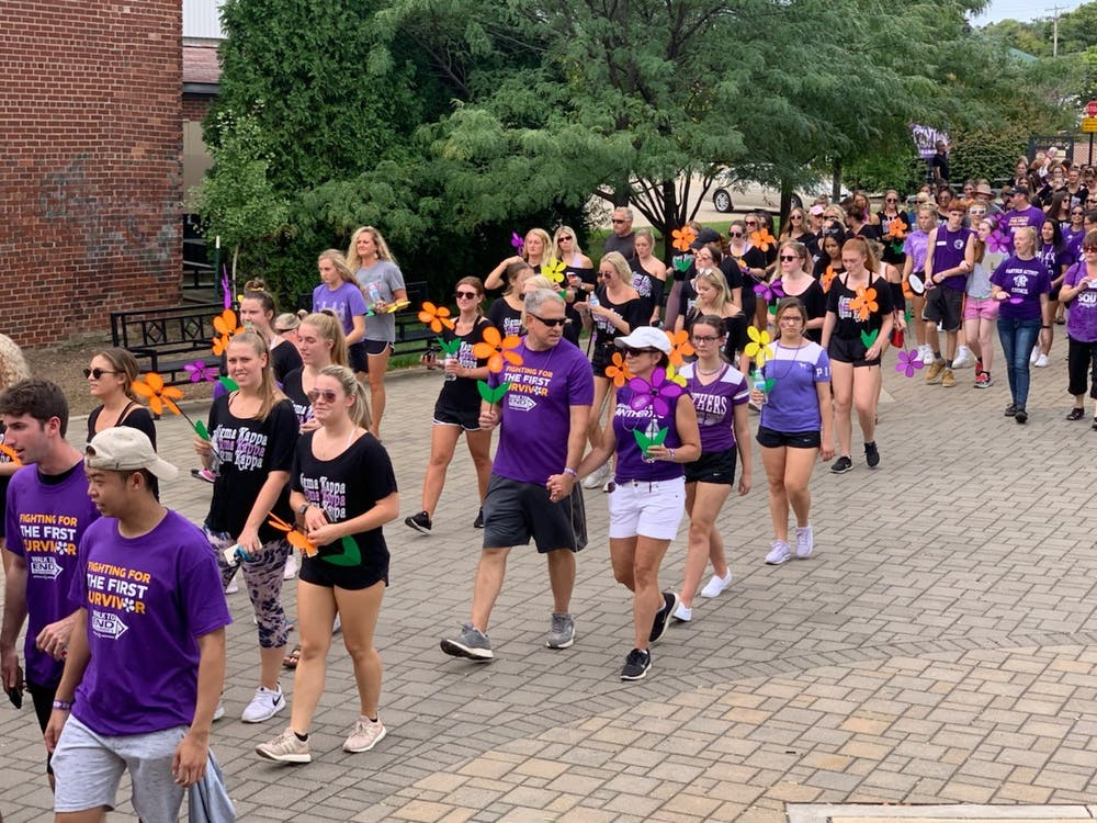 <p>Participants carry a flower representing their journey with the disease during the Walk to End Alzheimer&#x27;s on Sept. 15, 2019. The funds raised from the walk go directly to the Alzheimer's Association.</p>
