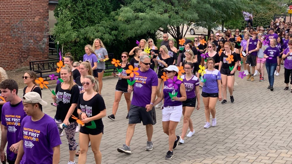 Participants carry a flower representing their journey with the disease during the Walk to End Alzheimer's on Sept. 15, 2019. The funds raised from the walk go directly to the Alzheimer's Association.