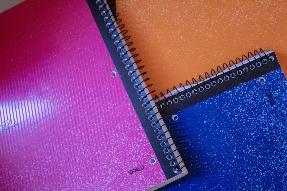 <p>A stack of notebooks sits on a desk. </p>