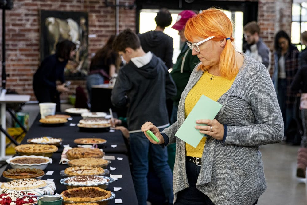 """<p>Pie tasting judge Kayte Young photographs an assortment of pies on the judge's table before the Bloomington Pie Contest on Nov. 3 in Dimension Mill. Young hosts a radio show called """"Earth Eats.""""</p>"""
