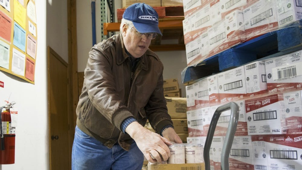 First United Methodist Church volunteer Steve Ulrey unloads cans of peaches on Wednesday at the Hoosier Hills Food Bank. The food bank serves six counties, including Monroe County, and will celebrate its 35th anniversary on Saturday.