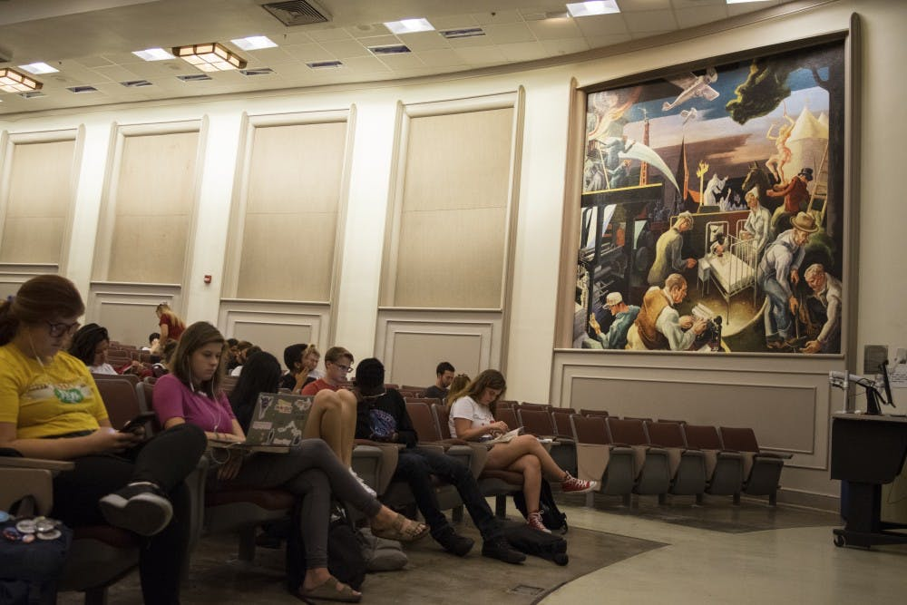 <p>Students wait for class to begin in Woodburn 100. The lecture hall contains a mural created by Thomas Hart Benton in 1933, which has created controversy for its depiction of hooded Ku Klux Klan members in its background.&nbsp;</p>