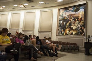 Students wait for class to begin in Woodburn 100. The lecture hall contains a mural created by Thomas Hart Benton in 1933, which has created controversy for its depiction of hooded Ku Klux Klan members in its background.