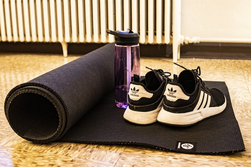 Adidas sneakers and a Camelbak water bottle sit on a yoga mat March 30 at University East apartments. Many IU students use their time while quarantining to practice self-care through activities such as yoga.