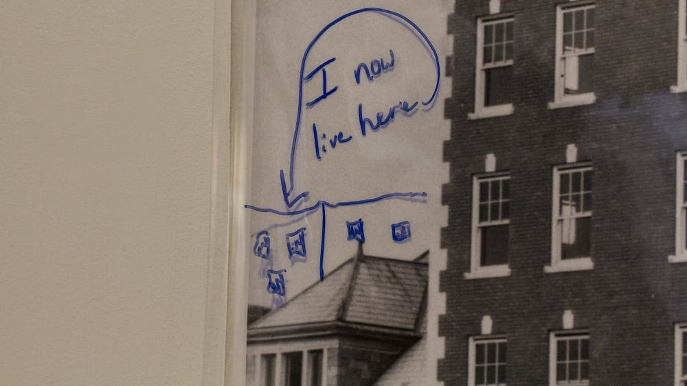 "A note left by a museum attendee is on display over one of the historic photographs as part of the ""Memories Shared: Photographs of Historic Bloomington"" exhibit Tuesday at the Mathers Museum of World Cultures. A sheet of plastic was placed over each of the photographs so museum attendees could draw pictures and leave notes. The exhibit runs until July 27."