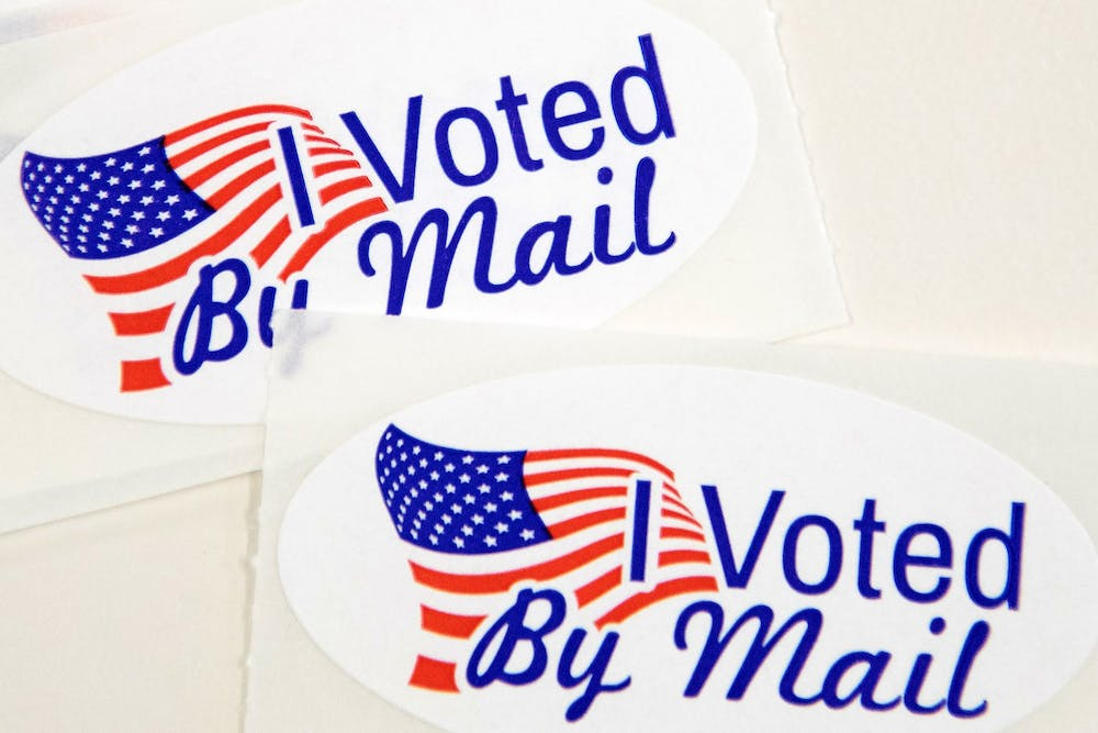 <p>Stickers that read &quot;I Voted By Mail&quot; sit on a table waiting to be stuffed into envelopes by absentee ballot election workers on Sept. 4 in Charlotte, North Carolina.</p>