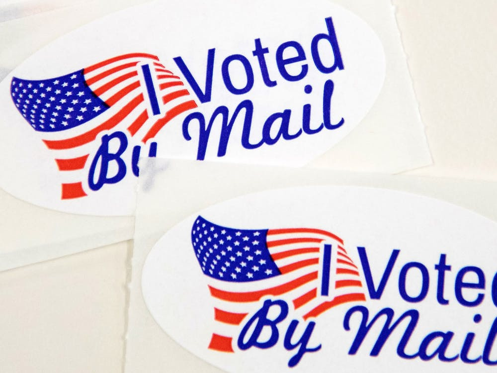 """Stickers that read """"I Voted By Mail"""" sit on a table waiting to be stuffed into envelopes by absentee ballot election workers on Sept. 4 in Charlotte, North Carolina."""