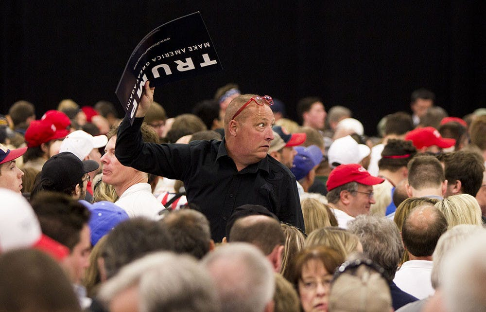A Trump supporter glances back to protestors being removed from a rally Wednesday at the Elements Financial Blue Ribbon Pavilion.  Many demonstrators were removed.