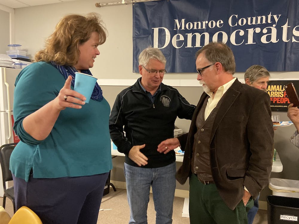 <p>Mayor John Hamilton, center, and Ron Smith shake hands while talking with Sue Sgambelluri on Tuesday night at the election watch party for the Monroe County Democrats. Smith won the election for Bloomington City Council District 3, and Sgambelluri won the District 2 race.</p>